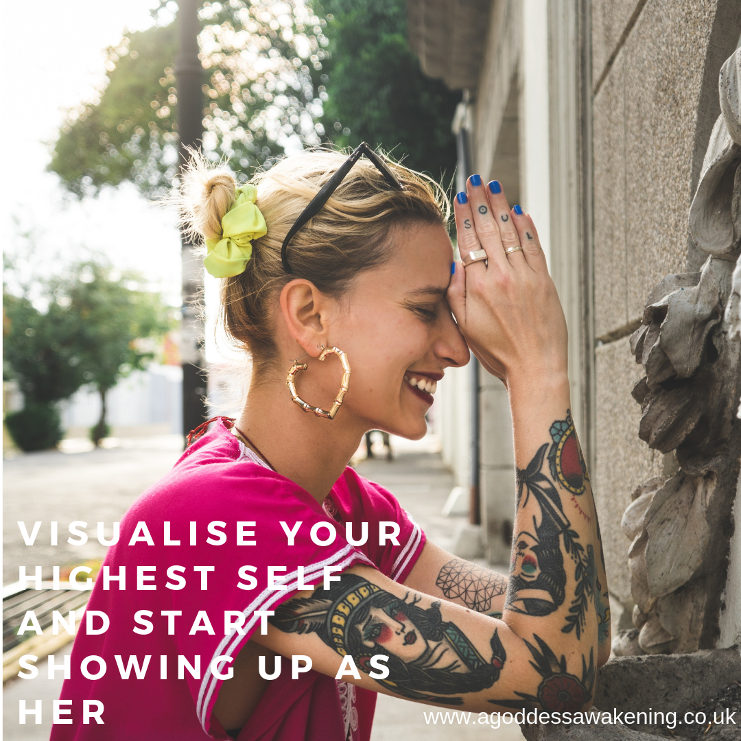 "Women with Tattoos, praying with a text saying ""visualise your highest self, and start showing up as her"" Photo by Miguel Bruna on Unsplash"